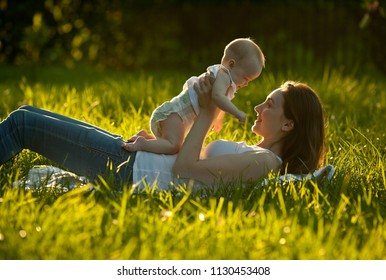 Cute cheerful baby lying on her mother and smilling