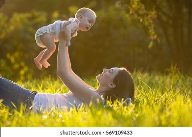 Cute cheerful baby on mother's hands at park