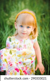Cute cheerful blond girl playing in the park