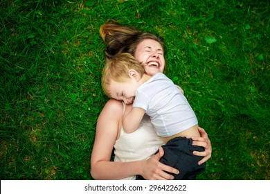 Cute cheerful child with mother play outdoors in park