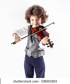Cute cheerful curly-haired boy in a waistcoat playing the violin. Close-up. Gray background.