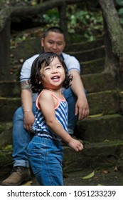 Cute cheerful daughter having fun with father at the park.