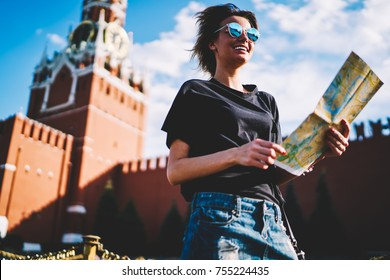 Cute cheerful female blogger enjoying vacation holidays during strolling at sunny urban setting.Successful pretty woman with destination map looking for sightseeing during summer walk in city