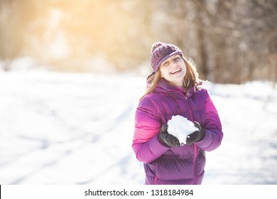 Cute cheerful girl with snow in her hands