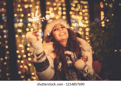 Cute cheerful girl with sparklers enjoying at the Christmas eve in the city street with a lot of holiday's lights.