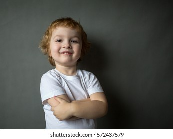 Cute cheerful happy curly-haired boy stands, hands clasped  and looking in to the camera. Close-up. Gray background.