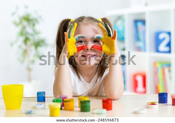 süßes junges Mädchen, das ihre Hände in hellen Farben lackiert