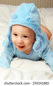 Cute cheerful  little baby boy in blue clothes.