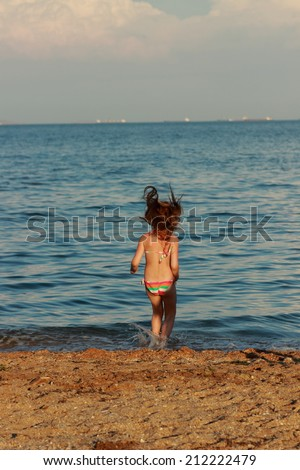 f23426bc3d Cute cheerful young girl in a bathing suit running and having fun at the  beach near