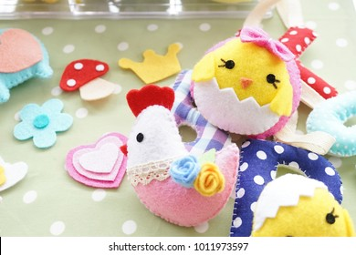 Cute chicken doll. Various toys for baby made from felt fabric or Happy Easter Day's decoration. Selective focus on chicken on top with pink bow.