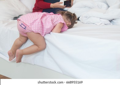 Cute child 1 year and 1 month in pink dress climbing on bed, Child development.