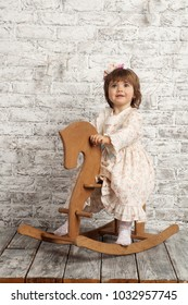 Cute child (a girl of two years old) in a flower dress and white pantyhose sits on a wooden horse against a white brick wall. Scandinavian style. Emotion `smile`