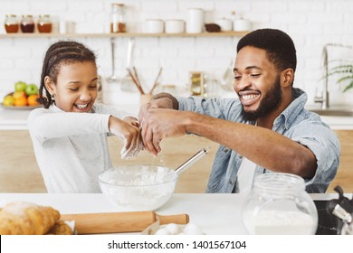 Cute child afro girl and his father making dough. having fun together at kitchen