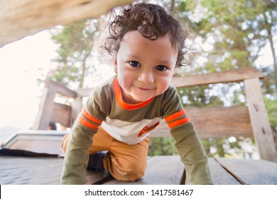 Cute child with big eyes crawling in a wooden game in the woods with the sun behind