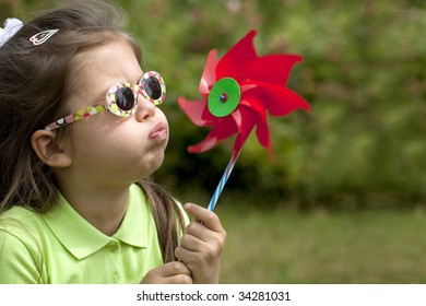 A cute child blowing a wind mill.