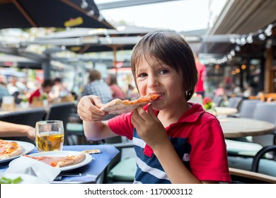 Cute child, boy, eating pizza in restaurant, happily smiling and biting