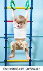 cute child boy hanging on gymnastic rings at home