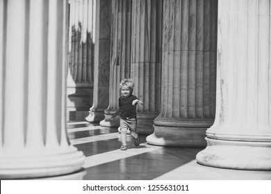 Cute child boy running between columns of ancient building in greek style. Kid walks on sunny day, boy on excursion, discovers world around him. Little boy happy to travel, on vacation, holidays