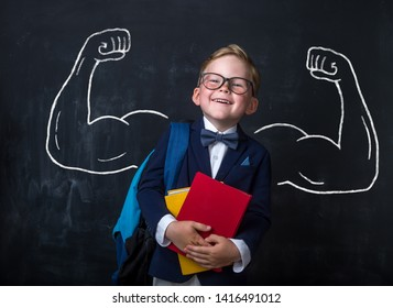 Cute child boy in school uniform and glasses. Go to school for the first time. Child with school bag and books. Kid in class room near chalkboard with muscles on it. Back to school