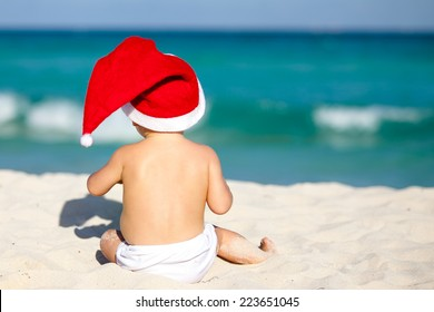 Cute child celebrating Christmas and New Year holidays in the Caribbean beach dressed as Santa.
