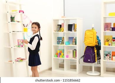 Cute child choosing school stationery in store