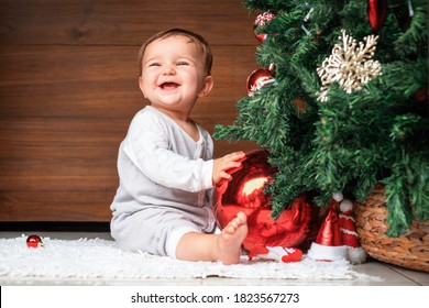 cute child with christmas tree.  happy baby sitting near a fir tree and holding a christmas ornament and smiling