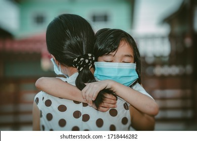Cute child daughter hugging mother on blurred home background, kids school back to home on mather's day, Asian children and mother wearing mask protect coronavirus 19 and pm 2.5 particle in air, Thai
