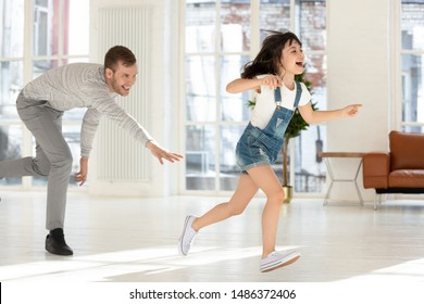 Cute child daughter running from happy dad catching playing tag and touch game at home, father chasing excited kid girl having fun enjoy leisure activity laughing spend time together in living room