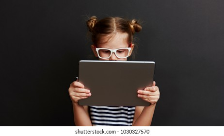 Cute child with digital tablet. Portrait of pretty little girl using web app for education.
