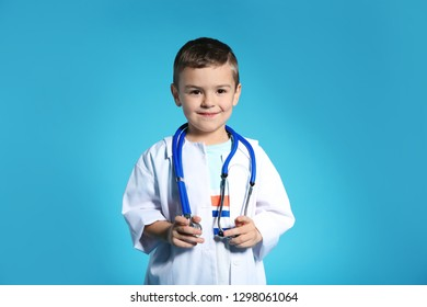 Cute child in doctor coat with stethoscope on color background