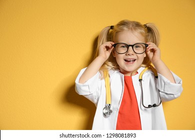 Cute child in doctor coat with stethoscope on color background. Space for text