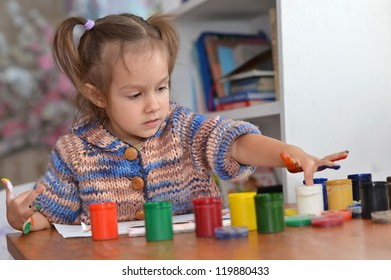 cute child draws paints at the table