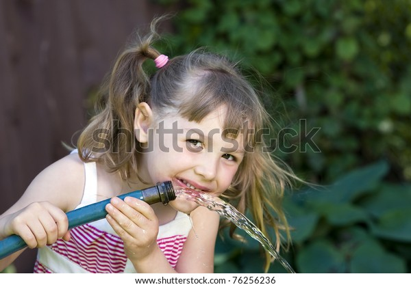 a cute child drinking from a garden hose