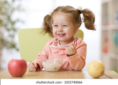 Cute child eating healthy food with the left hand at home