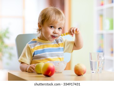 Cute child eating healthy food with with the left hand at home