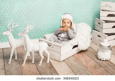 Cute child eating holly-cake and sitting in white box wearing aviator hat