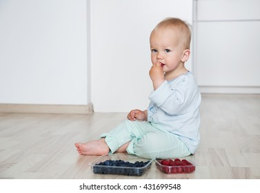 Cute child eats berries in the home interior