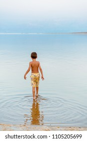Cute child entering into the Dead sea water for relaxing and enjoying. Family healthy vacation concept