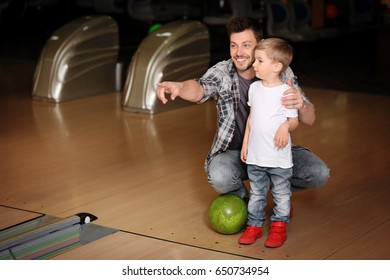 Cute child with father in bowling club