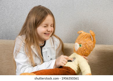 Cute child girl in the doctor's clothes playing with a stuffed cat at home.