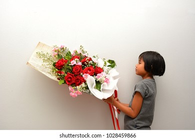 Cute child girl holding flower bouquet on her hands. Valentine 's day and mother 's day concept.