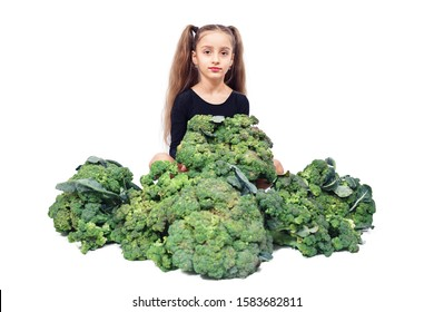Cute child girl in leotard sits among broccoli and holds it in her hands. Isolated over white background.