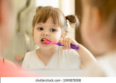 Cute child girl looking at mirror using toothbrush cleaning teeth in bathroom every morning and night.