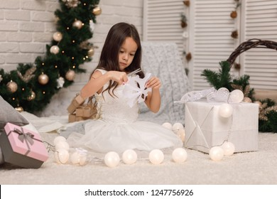 Cute child girl makes paper snowflakes for decoration Christmas tree at home