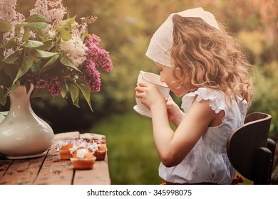 cute child girl on cozy outdoor tea party in spring garden with bouquet of lilacs, vintage style dress