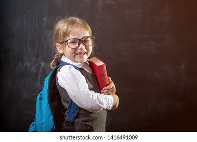 Cute child girl in school uniform and glasses. Go to school for the first time. Child with school bag and book. Kid indoors of the class room with blackboard on a background. Back to school