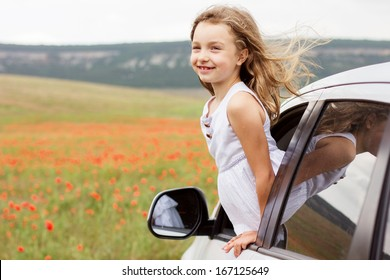 Cute child girl sitting inside a car on poppy field