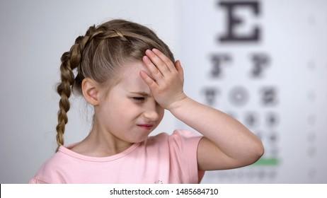 Cute child girl suffering headache, first myopia symptom, loss of eyesight