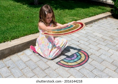 Cute child girl in tie dye dress playing with rainbow suncatcher outside. Fun crafting ideas for kids from recyclable items. Creative play with shadows. DIY concept