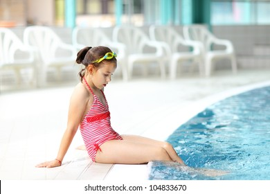 Cute child with goggles relaxing by swimming pool